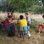 Groupe assis discutant sous un arbre